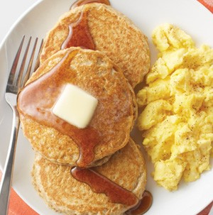 Small round pancakes topped with butter square and maple syrup with scrambled eggs on the side