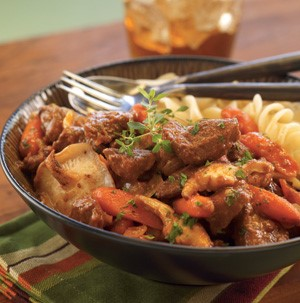 Beef, spiral pasta, and carrots in a bowl with a fork and a spoon