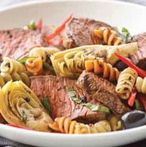 Plate filled with beef, pasta and artichokes and tossed in a balsamic vinaigrette