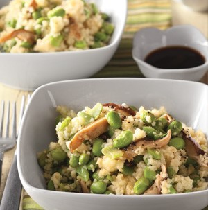 Couscous with edamame and sliced mushrooms in a white square bowl
