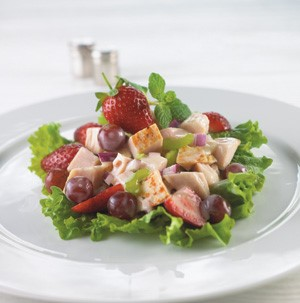 Chicken cubes with strawberries, grapes, and mint on a lettuce leaf