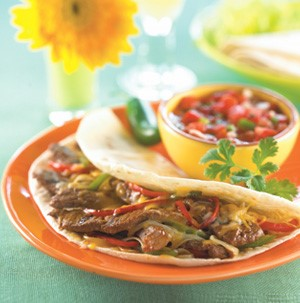 Shredded beef and pepper fajitas on an orange plate with pico de gallo in the background