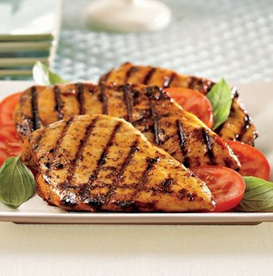 Grilled chicken with sliced tomatoes and basil leaves