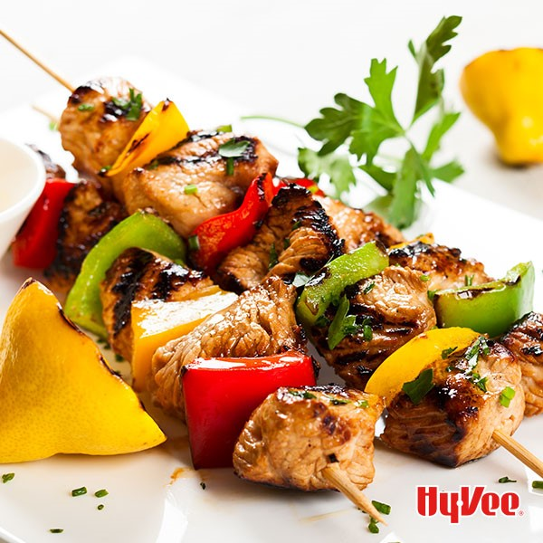 Dijon chicken and red, green and yellow bell peppers on wooden skewers