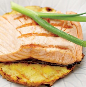 White plate with grilled salmon and garnished with green onion