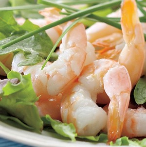 Grilled tail-on shrimp on a bed of mixed greens and garnished with fresh chives