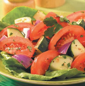Tomato wedges with red onions and cucumbers on top of a lettuce leaf
