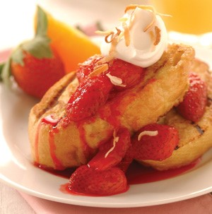 French toast topped with strawberries, whipped cream and toasted coconut shreds