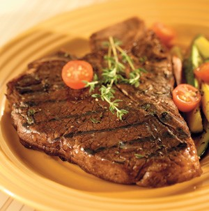T-bone steak grilled in balsamic garlic with grape tomatoes on a yellow plate