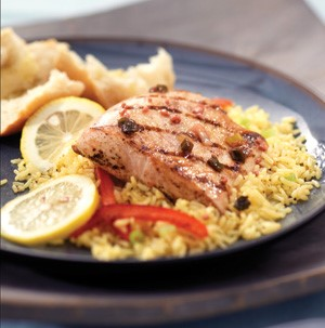 Rice topped with grilled mahi mahi fillet, sliced lemons, and sliced red bell peppers
