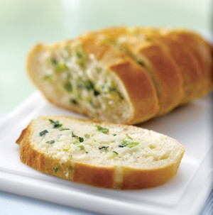 Sliced bread topped with fresh herbs and melted cheese