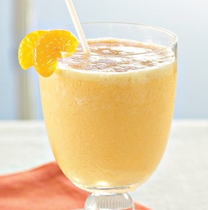 Glass filled with an orange-colored smoothie, garnished with orange slices and a straw