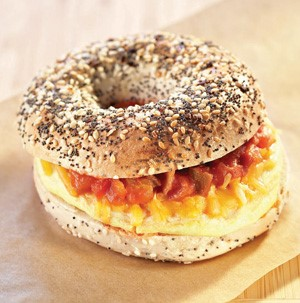 Egg, cheese and salsa sandwiched between a sliced everything bagel