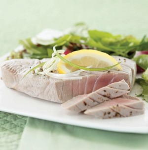 Poached sliced tuna garnished with green onions, white onions, and lemon wedge