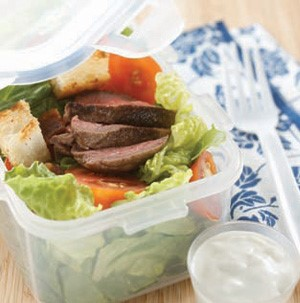 Plastic container filled with salad topped with blue cheese and steak