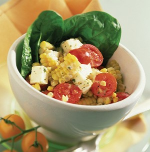 White bowl filled with corn, mozzarella cubes, halved tomatoes, and spinach leaves