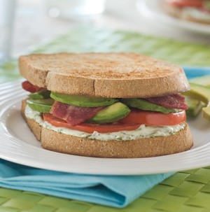 Bacon, tomato, avocado and basil-lime mayo sandwiched between two whole grain bread slices