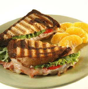 Marbled rye bread with cheese, tomato, turkey, lettuce, and a side of orange segments on a grey plate
