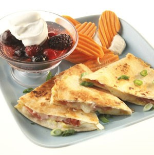 Blue plate topped with triangle-cut quesadillas, crinkle chips and mixed berries on the side