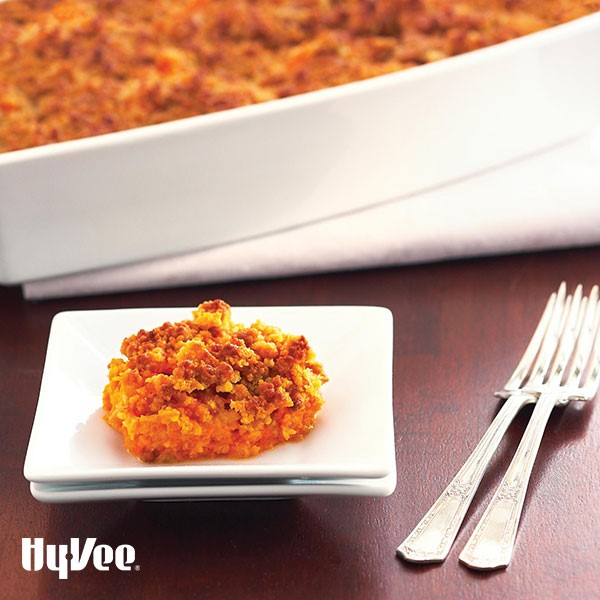 Small plate filled with baked mashed sweet potatoes layered with a crumb topping next to silver forks