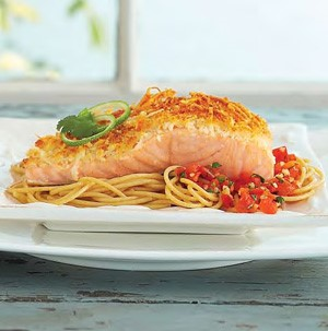 Parmesan-crusted salmon over red pepper salsa and angel hair pasta on a white plate