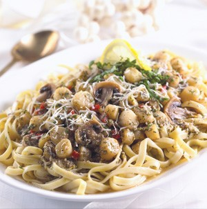 Platter of fettuccine noodles topped with scallops, mushrooms, bell pepper, pesto sauce and parmesan