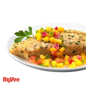 Baked tilapia with diced mango, red onion, and green pepper salsa and garnished with Italian parsley