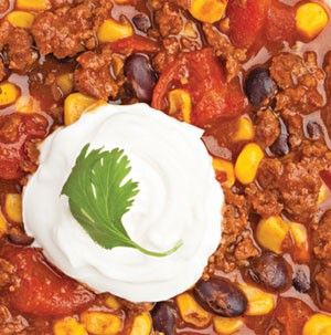 Black bean and corn chili garnished with sour cream and cilantro