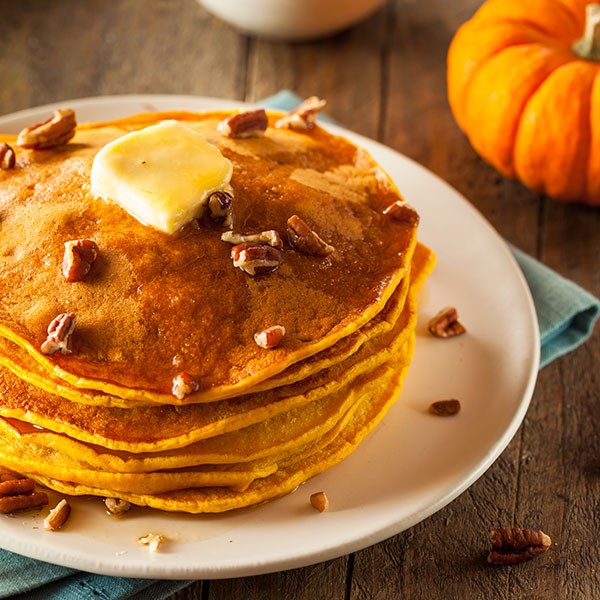 Stack of pumpkin pancakes topped with maple syrup, butter and pecans on a white plate
