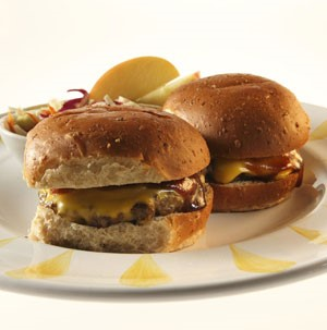 Plate of BBQ cheeseburger sliders with a side of coleslaw