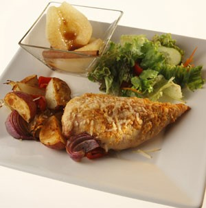 Chicken breast with baked cheese and sides of roasted red onions, potato wedges, poached pears, and lettuce salad