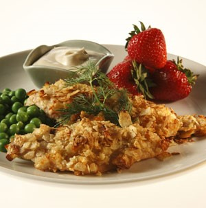 Tilapia covered in crunchy potato crust with peas and whole strawberries on the side