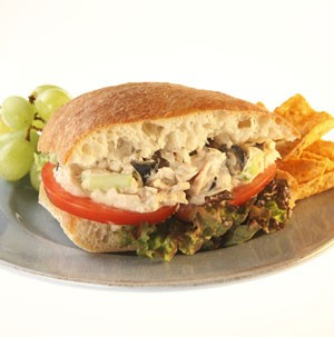 Sandwich filled with lettuce, sliced tomato, and tuna salad on a grey plate with chips and green grapes