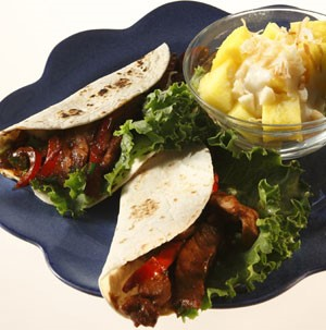 Two flour tortillas filled with sliced pork, peppers, and lettuce, with a side of diced pineapple on a blue plate