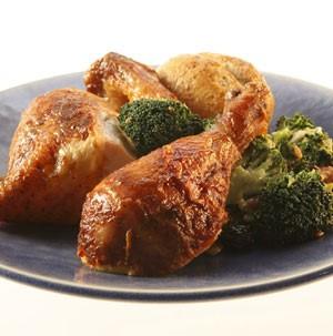Rotisserie chicken drumsticks on a dark blue plate with broccoli