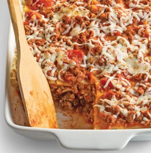 Lasagna in white serving dish with wooden spoon