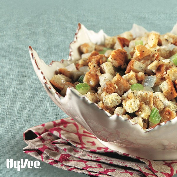 White serving dish filled with cubed bread, chopped white onion, and chopped celery