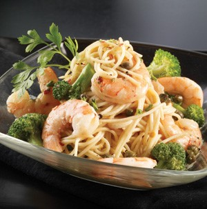 Spaghetti topped with shrimp, parsley, and broccoli