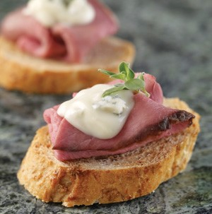 Sliced bread topped with roast beef and blue cheese sauce garnished with fresh thyme