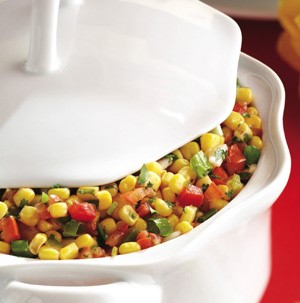 Corn kernels with bell peppers and green onions in a casserole dish