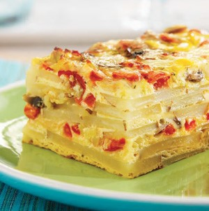 Baked layered potato strata with egg and cheese on green plate