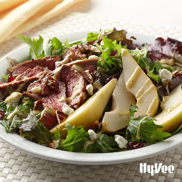 Mixed greens topped with sliced beef tenderloin, chopped pecans, crumbled cheese, dried cranberries, and sliced skin-on pears