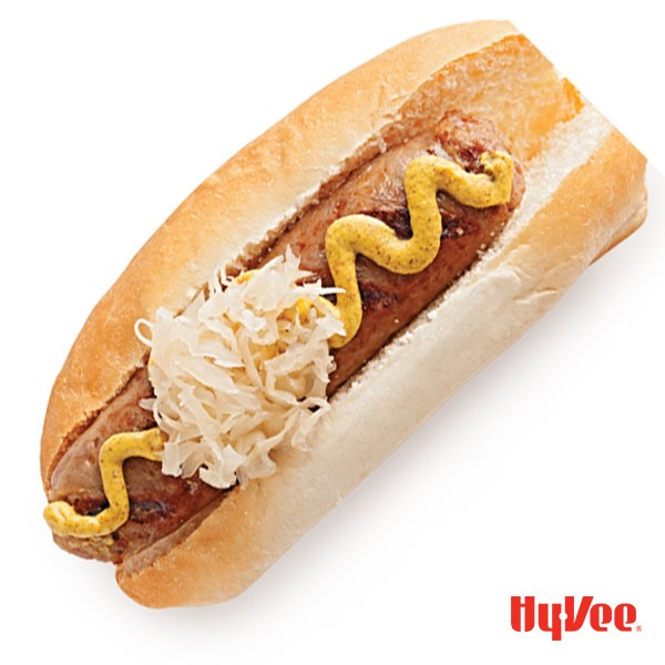 Brat and bun topped with mustard, onions and sauerkraut
