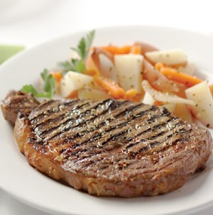 Grilled rib eye steak on a white plate with chopped potatoes, carrots, and fresh parsley