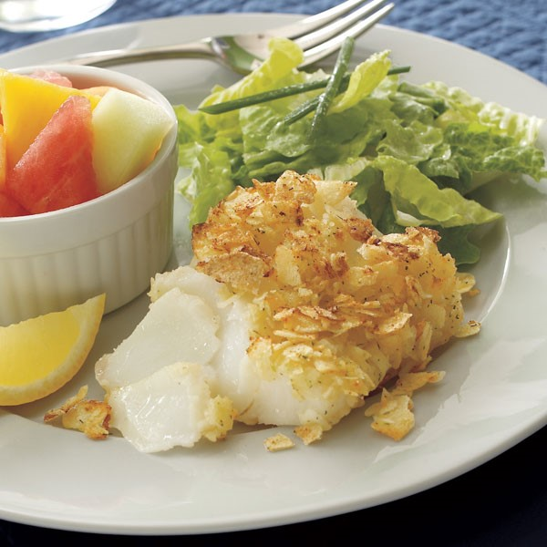 Plate of parmesan-crusted halibut served with lettuce and fruit