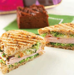 Sliced turkey grilled paninis  filled with vegetables, cheese, and broccoli