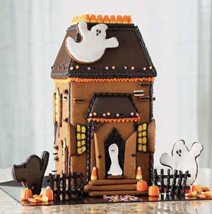 Gingerbread house decorated with candy corn and ghost cookies