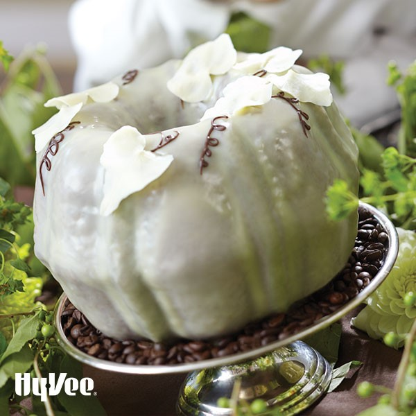 White chocolate bundt cake decorated with flour petals and chocolate vines surrounded by green and white flowers
