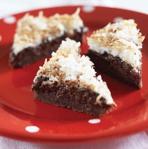 Chocolate brownies topped with shredded coconut on a red plate