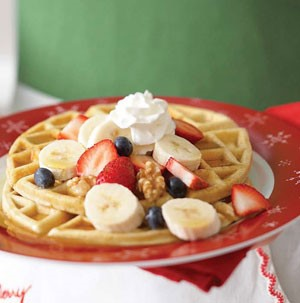 Two Waffles topped with Strawberries, Sliced Bananas, and Blueberries with Whipped Cream on Top